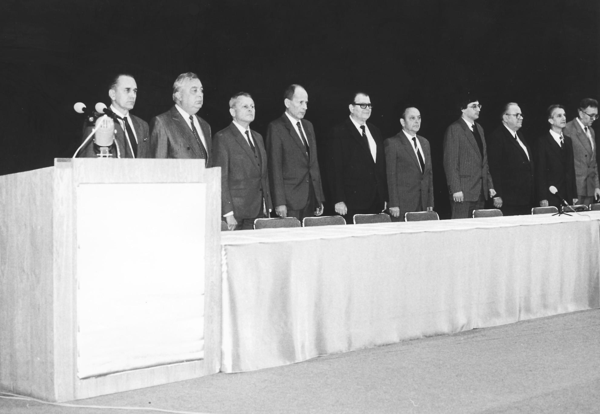 Na snímku z prvního slav ostního shromáždění LF UK v Plzni po listopadu 1989 je zachycena část nově rekonstruované vědecké rady fakulty a její slavnostní hosté, např. první trojici zprava tvoří první rektor Západočeské univerzity doc. MUDr. J. Holenda, CSc., polistopadový děkan LF UK a přednosta chirurgické kliniky v létech 1990–1999 prof. MUDr. J. Valenta, DrSc., a prorektor Karlovy univerzity prof. MUDr. Z. Lojda, DrSc. Doc. MUDr. Milan Schück, CSc., stojí čtvrtý zleva a vlevo od něho je zachycen první předseda Akademického senátu LF UK v Plzni a  olistopadový přednosta I. interní kliniky prof. MUDr. K. Opatrný, DrSc.