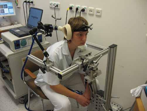 Repetitivní transkraniální magnetická stimulace pravého cerebella při bezrámové navigaci. Pomocí reflexních terčů, které jsou umístěny na cívce a na hlavě pacienta, kamerovému systému (není na snímku) a počítačovému softwaru může být stimulační cívka přesně zaměřena na cílové struktury (cívka patrná z pravé dorzální strany hlavy pacienta).