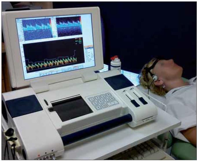 TCD monitorovací přístroj s monitorovací 2MHz sondou upevněnou v monitorovací čepici. Na monitoru TCD křivka z a. cerebri media vpravo.