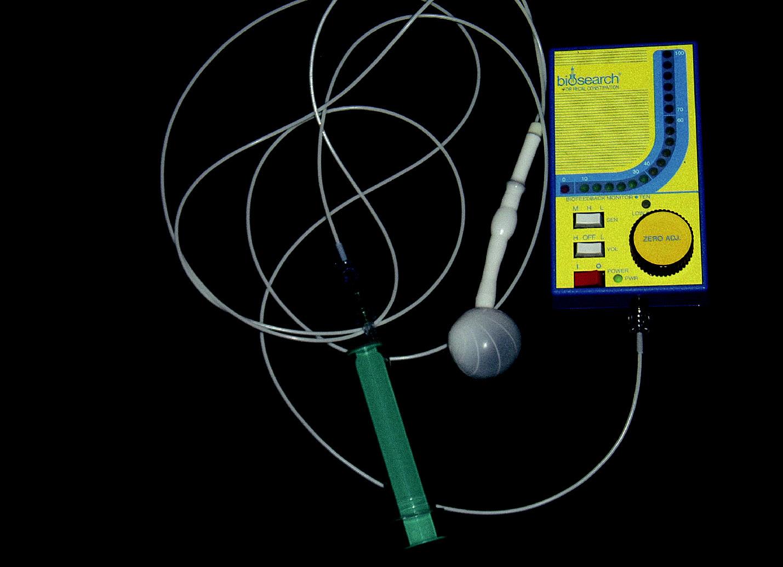 Přístroj k biofeedbacku. Na konci sondy je balónek, který se v rektu nafukuje, zhruba vprostřed sondy je senzor, který snímá tlaky z konečníku. Na přístroji malá světýlka – pfii relaxaci svítí zeleně (čím větší relaxace, tím více světýlek svítí) nebo červeně (při patologické kontrakci).