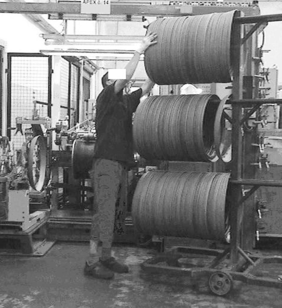Poloha horních končetin u dělníka při výrobě pneumatiky