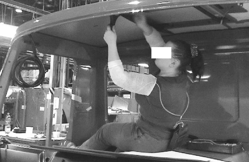 Poloha horních končetin u dělnice při montáži stropu kabiny auta