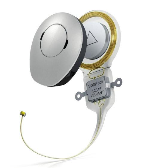"""VibrantSoundbridge™ společnosti MED-EL. Zobrazen spolu se zvukovým procesorem typu mimo boltec, """"off-the- -ear"""". Aktuator nazvaný Floating Mass Transducer™ (FMT) je na konci elektrodového svodu v levé dolní části obrázku. (Zdroj: MED-EL, Innsbruck, Rakousko.)"""