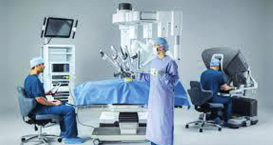 Robotem asistovaná operace systémem daVinci Xi – robotická konzole se sedícím chirurgem, perioperační sestra u robotického systému s operačními nástroji, počítačová věž s monitory a sedící anesteziolog. Zdroj: Intuitive Surgical