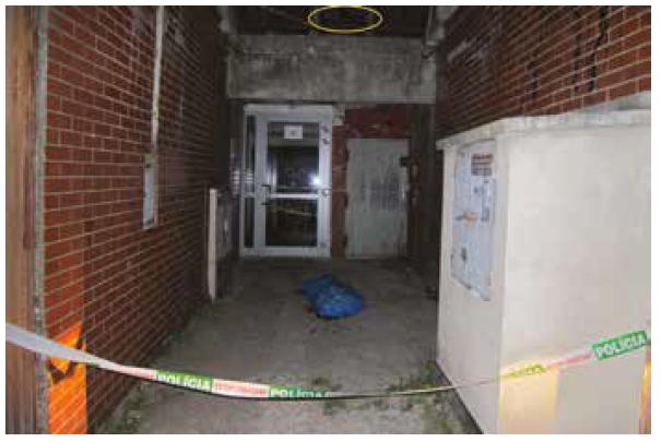 Pohľad na telo na mieste nálezu prikryté plastovým vrecom pred vchodom do suterénu panelového domu, na zábradlí nad telom dolná časť prevesených nohavíc (elipsa).
